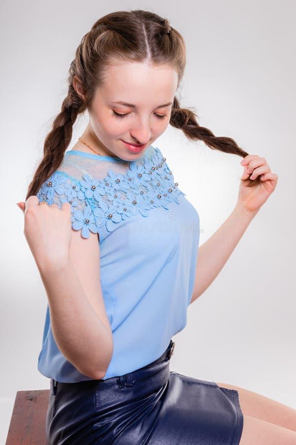 Jeune fille avec les yeux abaissés tenant ses tresses photographie stock