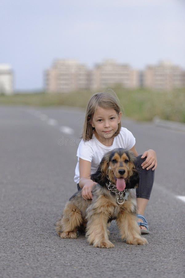 Jeune fille avec son chien dans la route image stock
