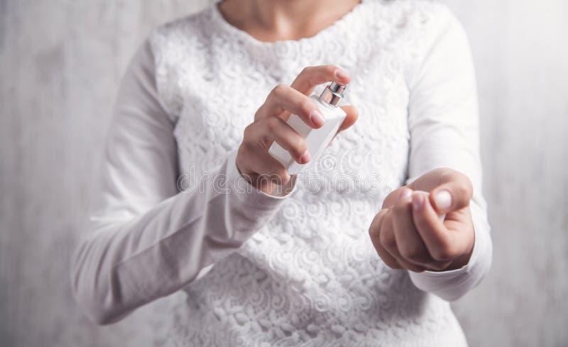 Jeune fille avec une bouteille de parfum Application du parfum image stock
