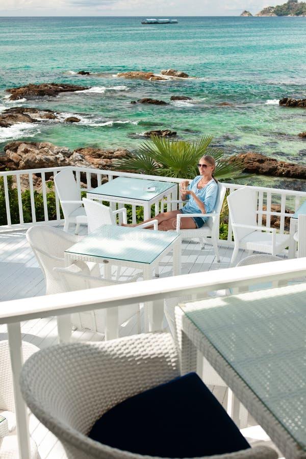 Jeune fille ayant la pause-café en café de vue d'océan image stock