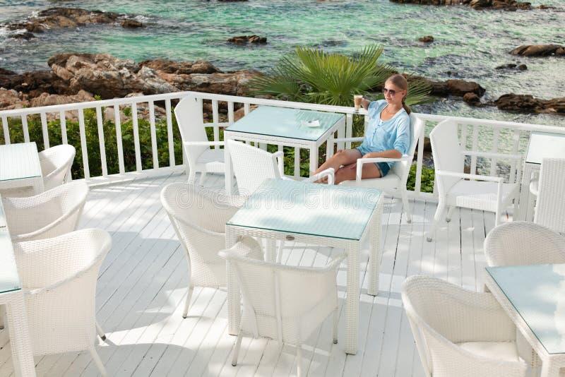 Jeune fille ayant la pause-café en café de vue d'océan images stock
