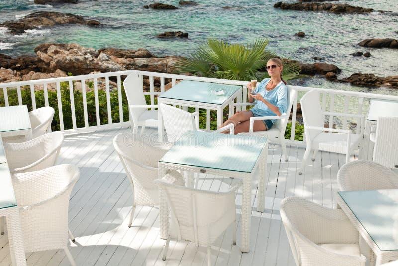 Jeune fille ayant la pause-café en café de vue d'océan photo libre de droits