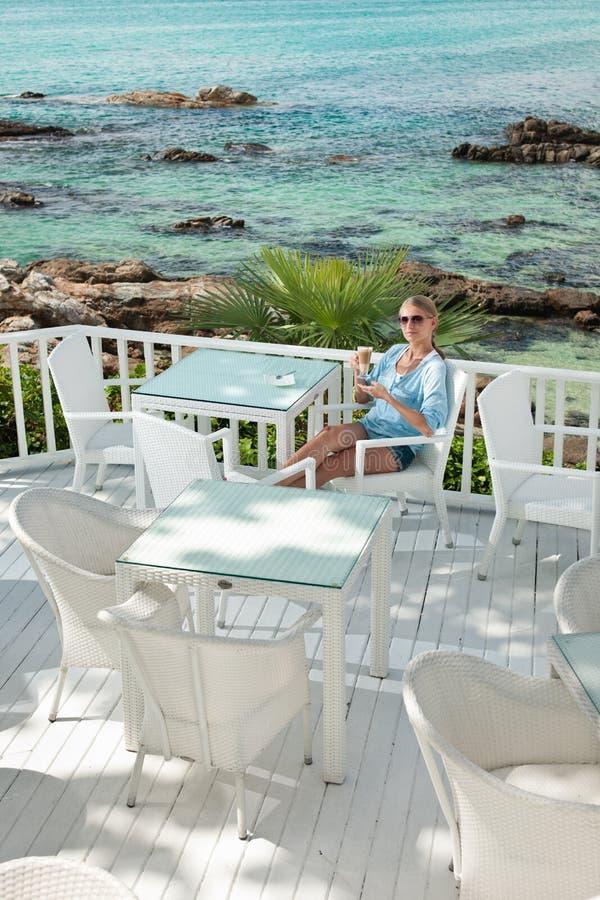 Jeune fille ayant la pause-café en café de vue d'océan images libres de droits