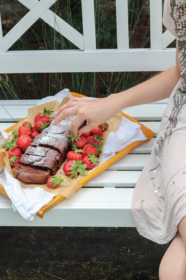Jeune fille ayant un pique-nique sur un banc de jardin avec le gâteau fait maison et les fraises fraîches images libres de droits