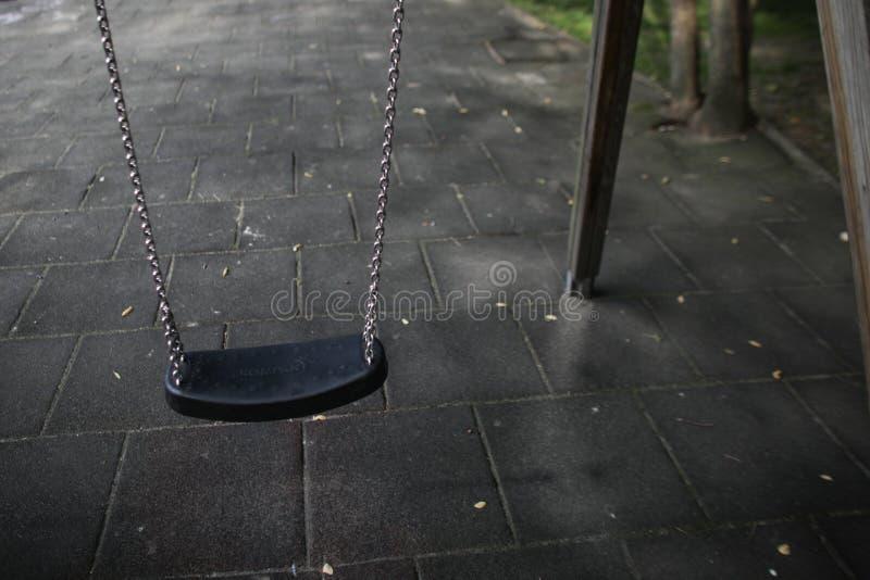 Jeune fille balançant dans un terrain de jeu d'enfants sans n'importe qui autour photographie stock libre de droits