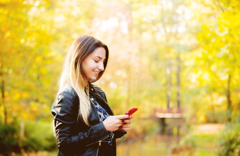 Jeune fille blanche à l'aide d'un téléphone portable dans un parc image stock