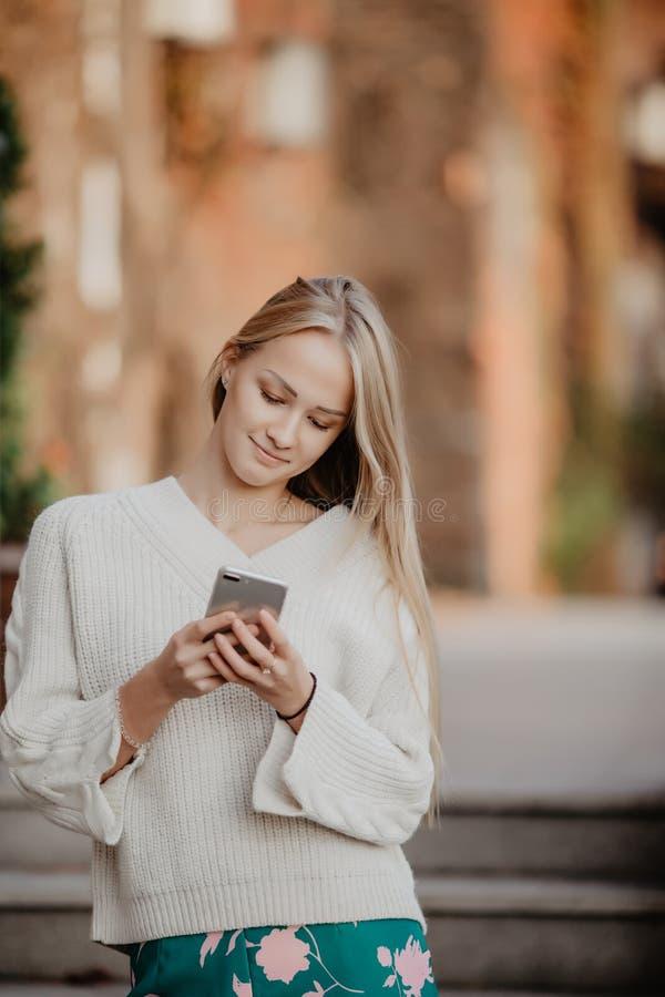 Jeune fille blonde à l'aide du téléphone, dehors Belle jeune femme dactylographiant au téléphone dans une ville pendant le jour e photographie stock