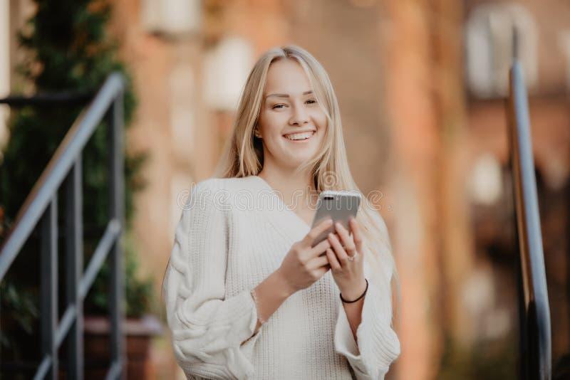 Jeune fille blonde à l'aide du téléphone, dehors Belle jeune femme dactylographiant au téléphone dans une ville pendant le jour e photos libres de droits