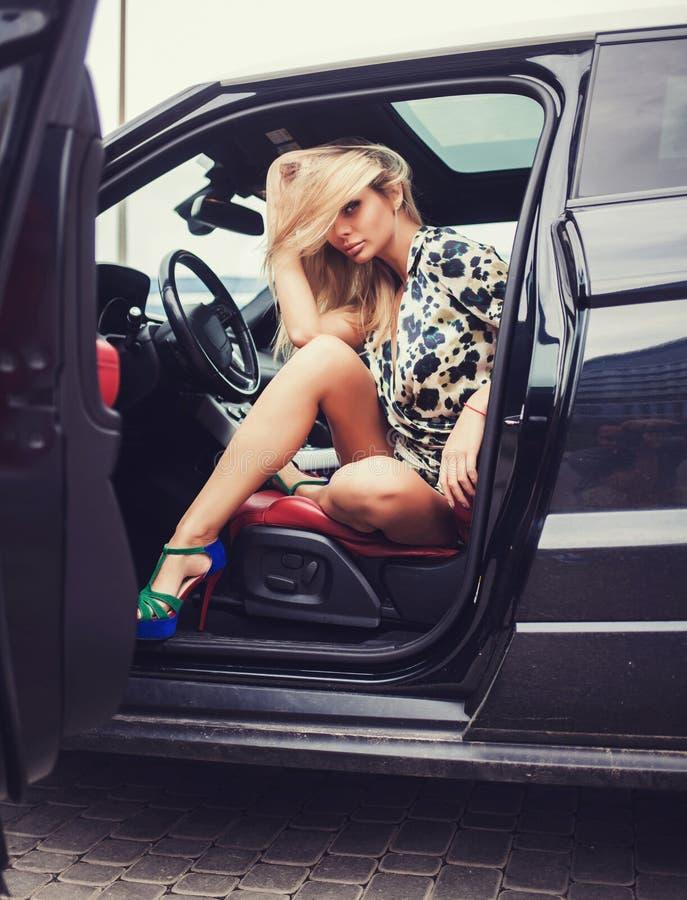 Jeune fille blonde à la roue de la voiture de sport image stock