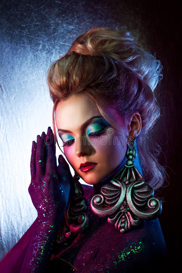 Jeune fille blonde attirante dans l'art-maquillage lumineux, hauts cheveux, peinture de corps Fausses pierres et scintillement photo stock