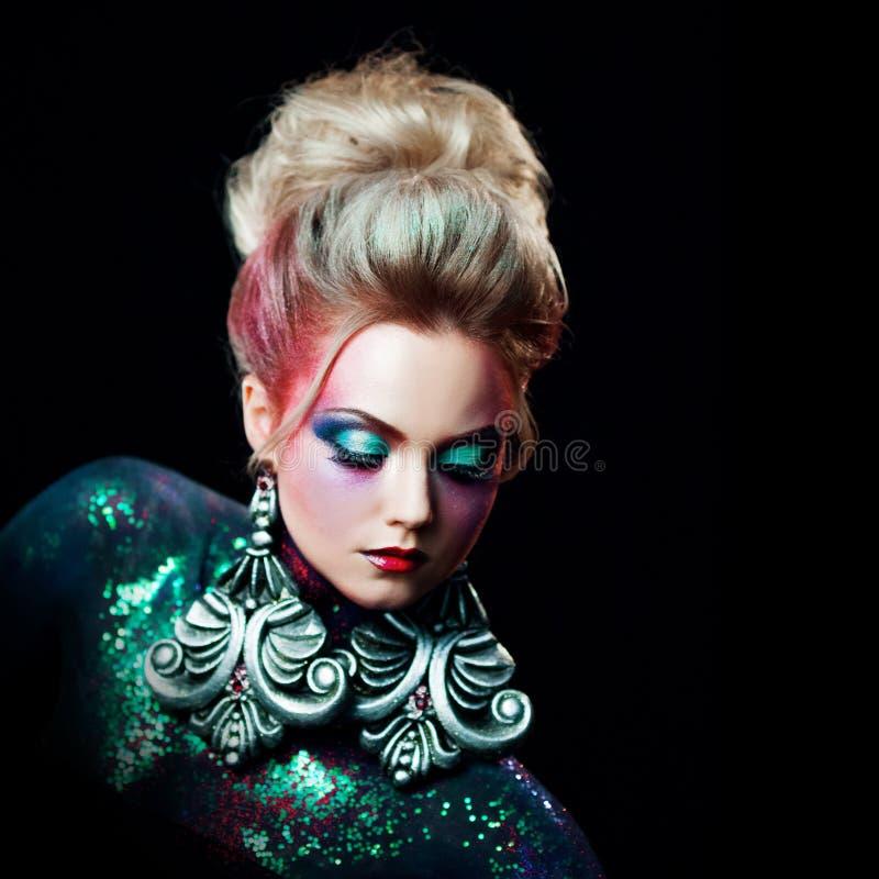 Jeune fille blonde attirante dans l'art-maquillage lumineux, hauts cheveux, peinture de corps Fausses pierres et scintillement photographie stock libre de droits