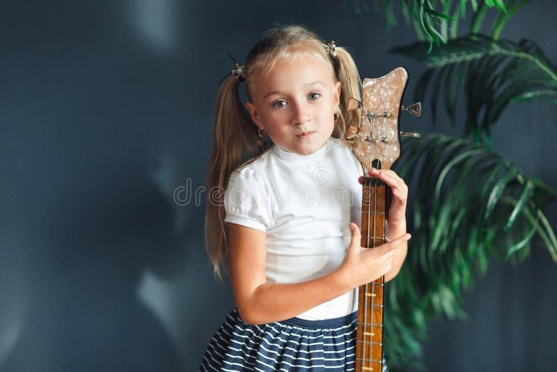 Jeune fille blonde avec des queues en T-shirt, jupe et sandales blancs avec la guitare électrique à la maison regardant la caméra photo libre de droits
