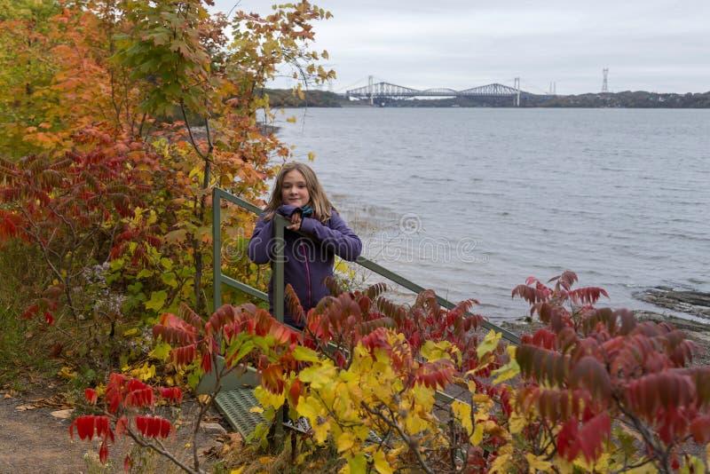Jeune fille blonde avec les cheveux ébouriffés par le vent se penchant sur la balustrade d'escalier image stock
