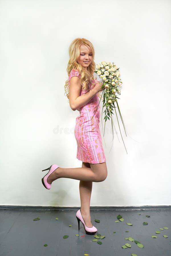 Jeune fille blonde avec un bouquet de flux photographie stock libre de droits