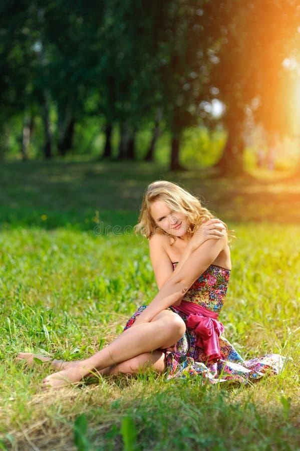 Jeune fille blonde dans la robe colorée lumineuse posant le mensonge sur l'herbe en parc d'été dans les rayons du soleil lumineux photographie stock