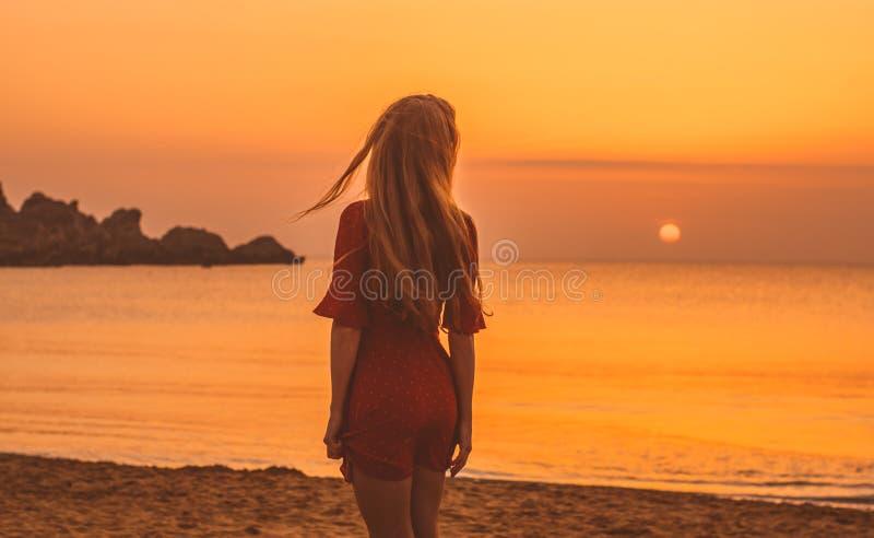 Jeune fille blonde dans la robe rouge sautant le soir sur la plage photos stock