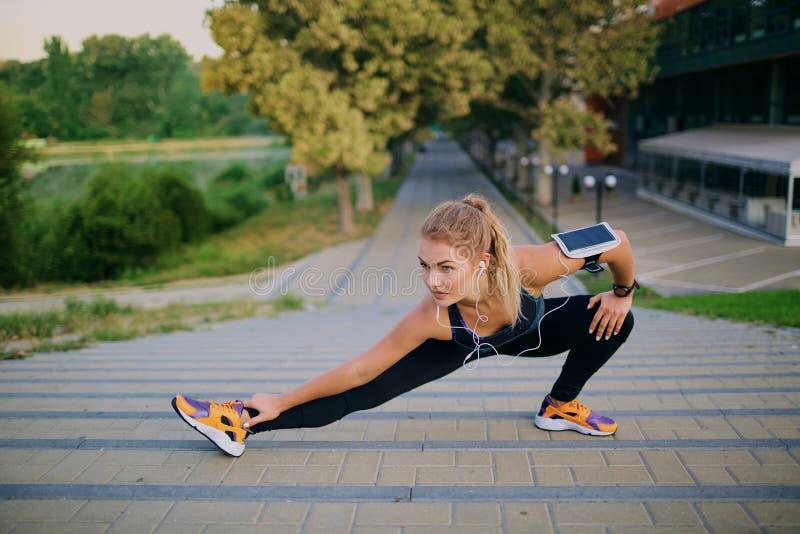 Jeune fille blonde faisant l'échauffement en parc l'automne image stock