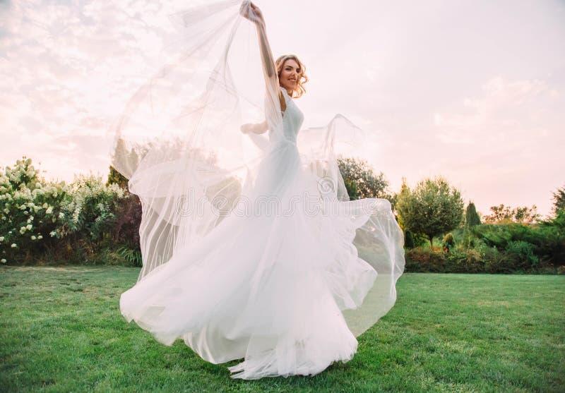 Jeune fille blonde heureuse dans une longue lumière blanche étonnante élégante de mariage et des mouvements giratoires et des sou images stock