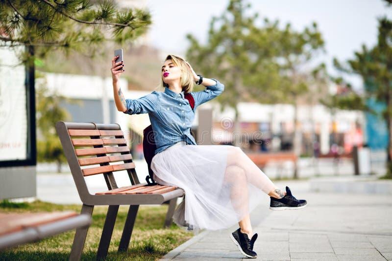 Jeune fille blonde mignonne avec les cheveux courts et les lèvres roses lumineuses se reposant sur un banc en bois faisant un sel images stock
