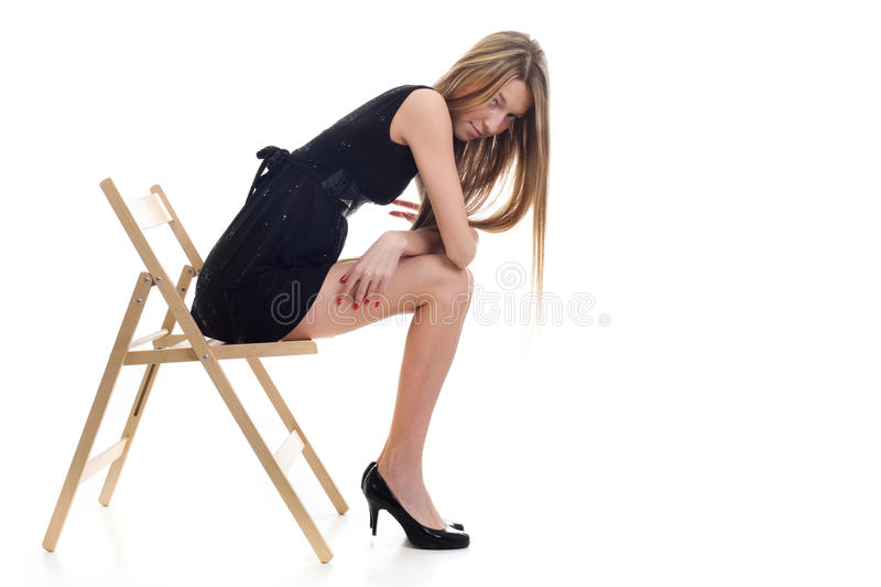 Jeune fille blonde s'asseyant sur une présidence image libre de droits