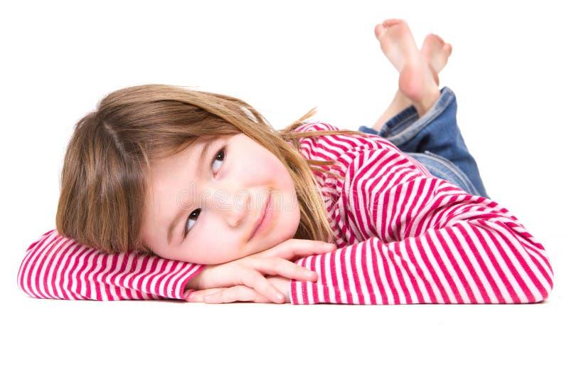 Jeune fille blonde se trouvant sur le plancher photographie stock libre de droits