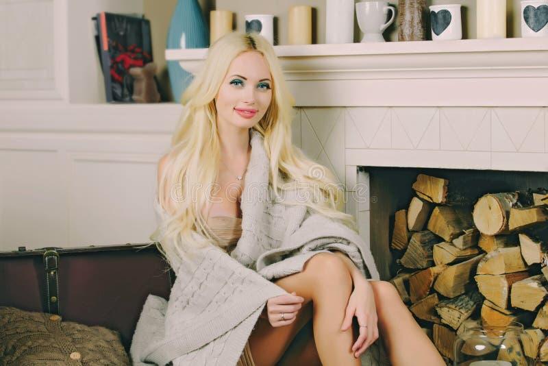 Jeune fille blonde sexy aux cheveux longs, aux lèvres bouffantes et aux gros seins. Fille assise près de la cheminée avec un pl photographie stock libre de droits