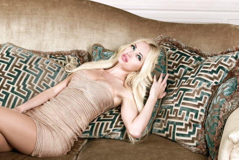 Jeune fille blonde sexy aux cheveux longs, aux lèvres bouffantes et aux gros seins, dans une belle robe dorée, posant dans le stu images stock