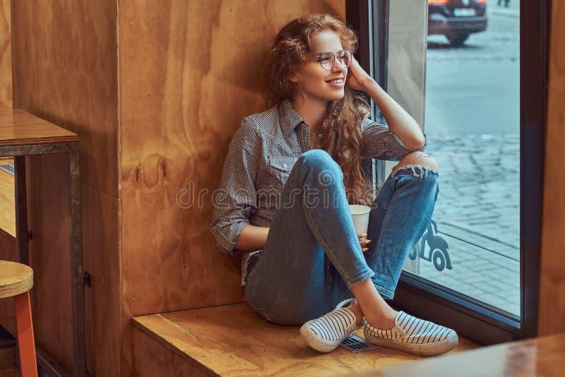 Jeune fille bouclée rousse heureuse portant les vêtements sport et les lunettes se reposant sur un filon-couche de fenêtre avec d photos stock