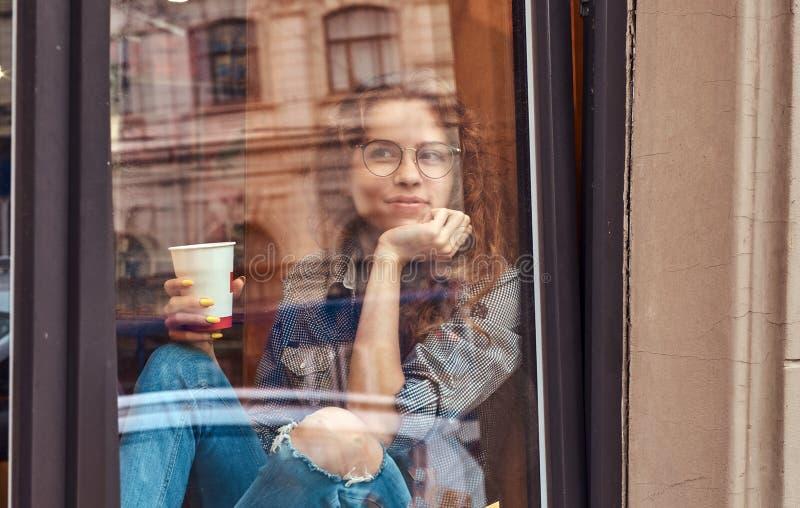 Jeune fille bouclée rousse portant les vêtements sport et les lunettes se reposant sur un filon-couche de fenêtre avec du café à  photos stock
