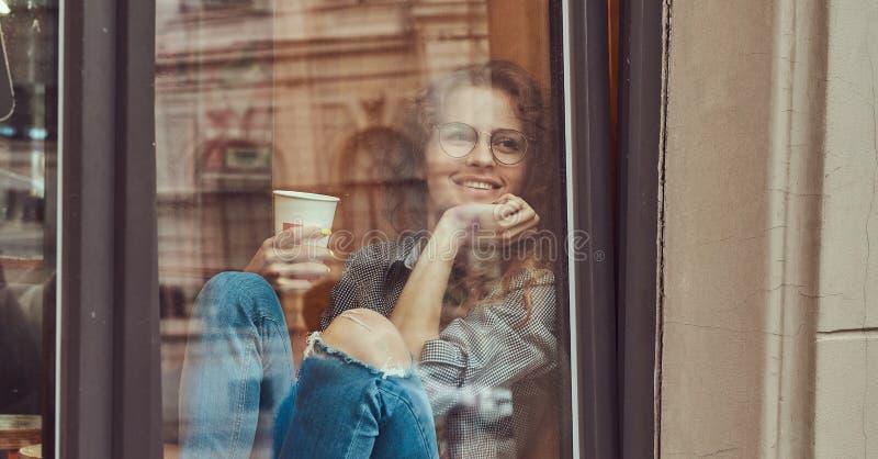 Jeune fille bouclée rousse portant les vêtements sport et les lunettes se reposant sur un filon-couche de fenêtre avec du café à  images stock