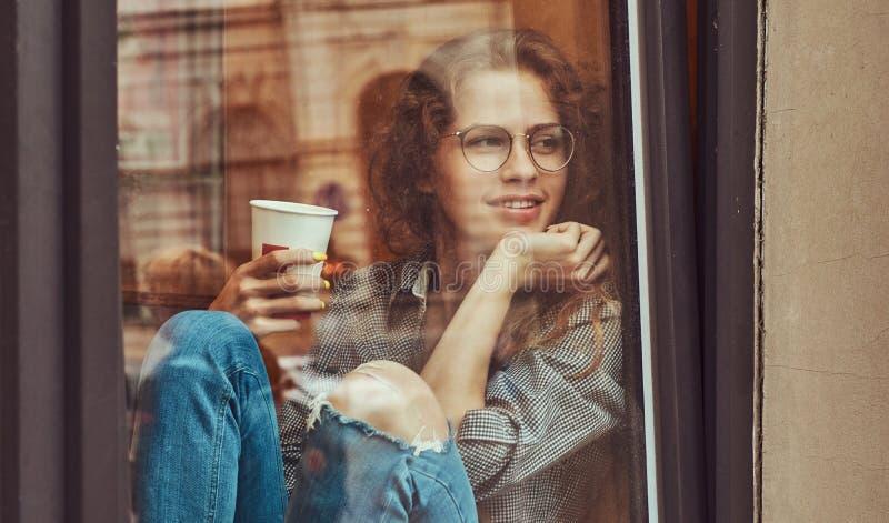 Jeune fille bouclée rousse portant les vêtements sport et les lunettes se reposant sur un filon-couche de fenêtre avec du café à  photos libres de droits