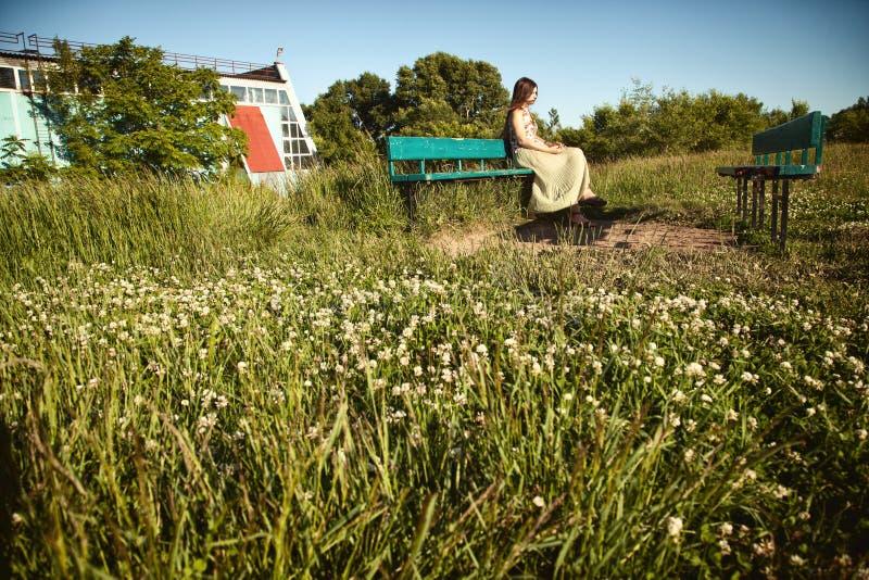 Jeune fille calme s'asseyant sur un banc dans un domaine avec l'herbe et les wildflowers images libres de droits