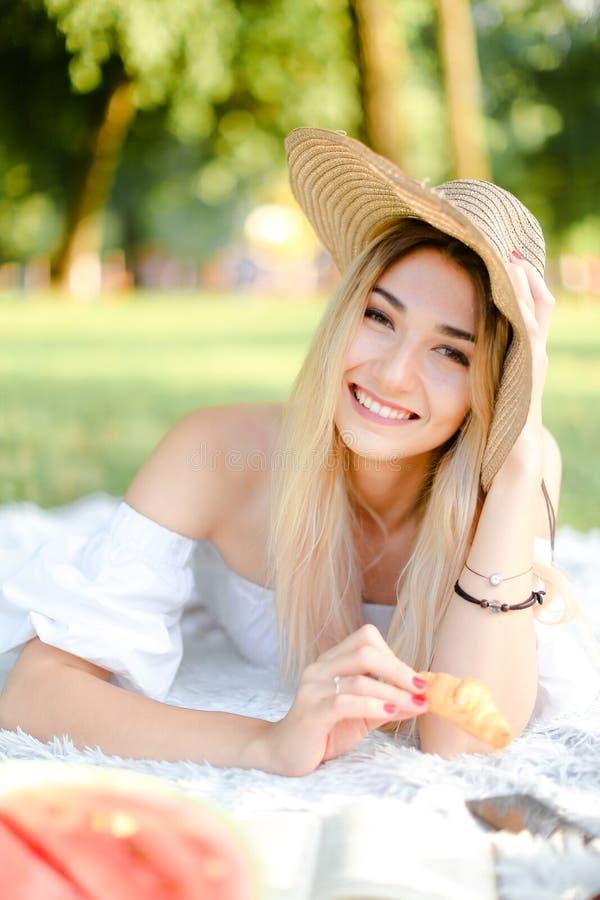 Jeune fille caucasienne dans le chapeau maintenant le croissant, se trouvant dans le parc sur le plaid et le livre de lecture photo stock