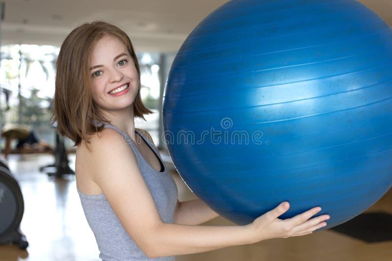 Jeune fille caucasienne de sourire de femme tenant une boule gymnastique bleue au gymnase, faisant l'exercice de pilates de séanc photo stock