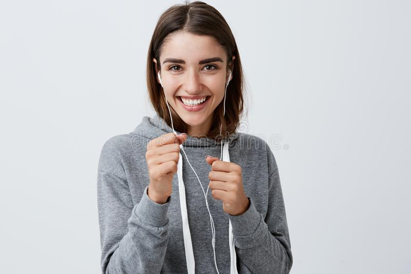 Jeune fille caucasienne drôle belle heureuse avec de longs cheveux foncés dans le hoodie gris occasionnel souriant avec des dents photographie stock