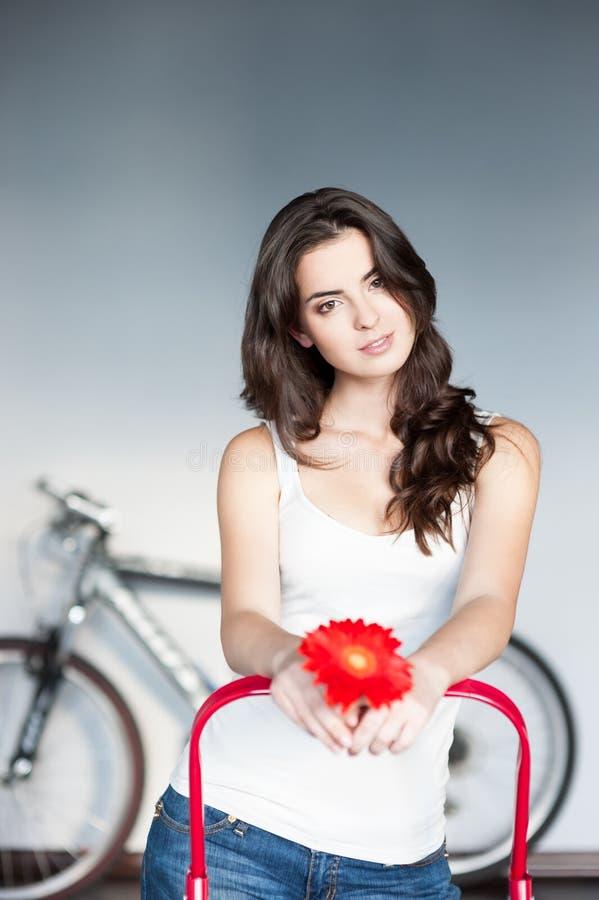 Jeune fille caucasienne occasionnelle avec la fleur rouge image stock