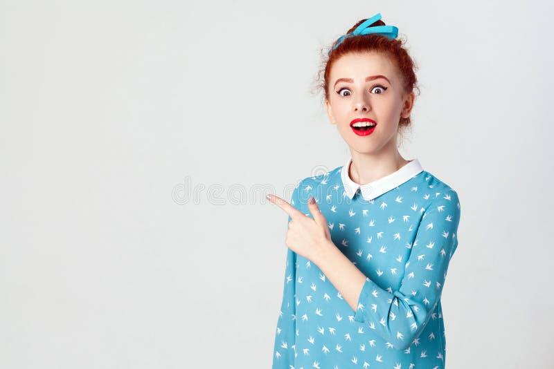 Jeune fille caucasienne rousse enthousiaste avec le noeud de cheveux dirigeant son index en longueur, soulevant des sourcils photo stock