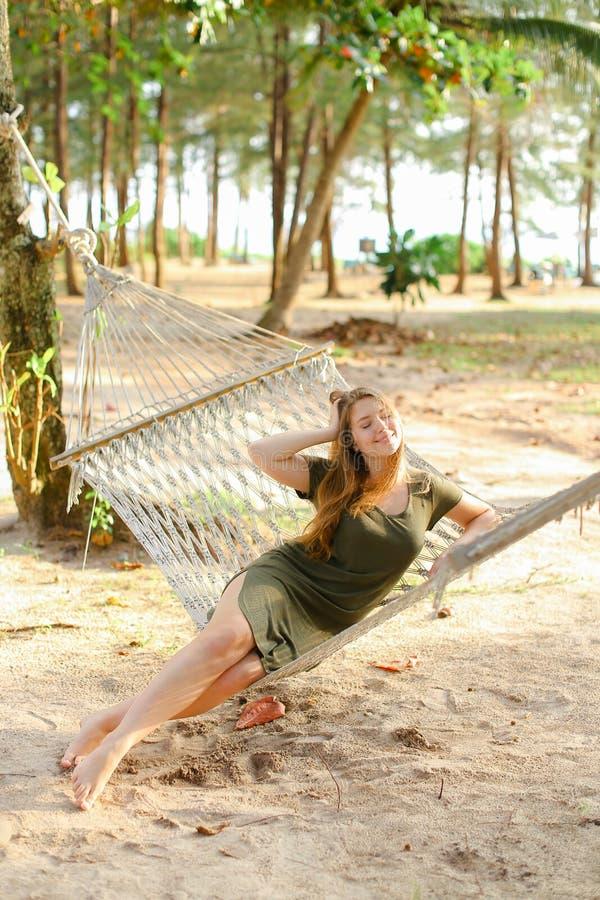 Jeune fille caucasienne s'asseyant nu-pieds sur l'hamac, le sable et les arbres en osier à l'arrière-plan images stock