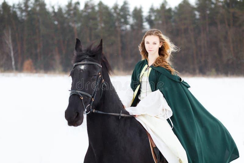 Jeune fille chez le cheval blanc de robe et d'équitation de cap photo libre de droits