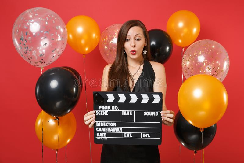 Jeune fille choquée dans la célébration noire de robe, regardant sur la claquette noire classique de cinéma dans des mains sur le image libre de droits