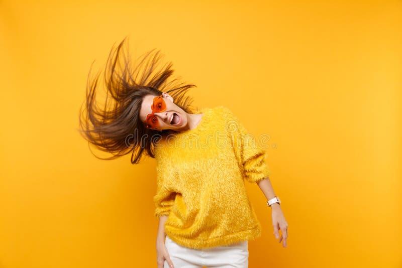 Jeune fille comique choquée dans le chandail de fourrure, verres oranges de coeur dupant autour dans le studio, sautant avec les  images stock