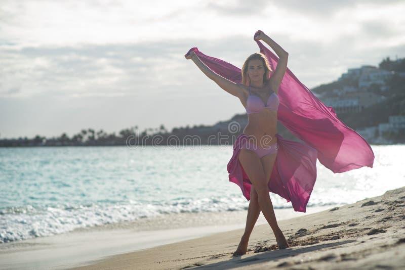 Jeune fille convenable et sportive posant sur une plage avec la soie volante rose images stock
