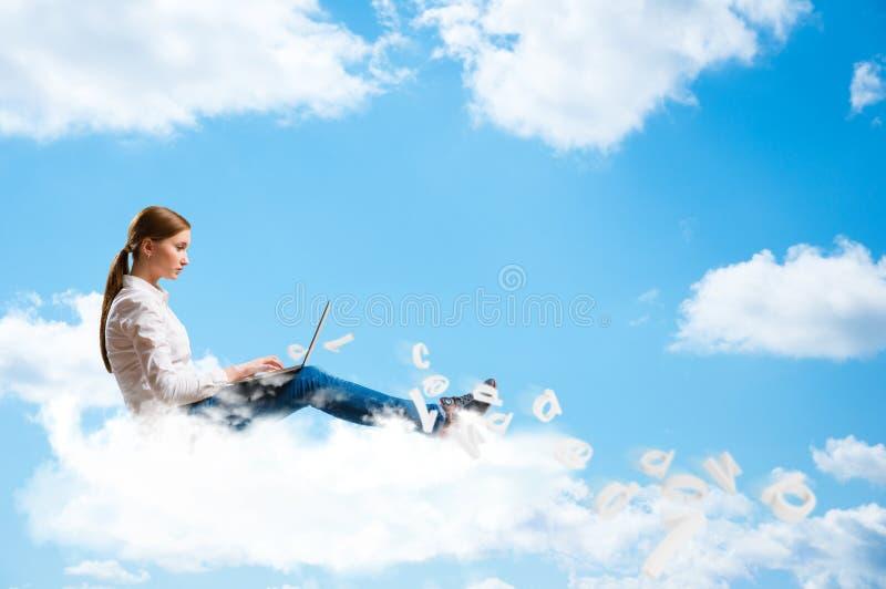 Jeune fille courant dans les nuages avec un ordinateur portable image stock