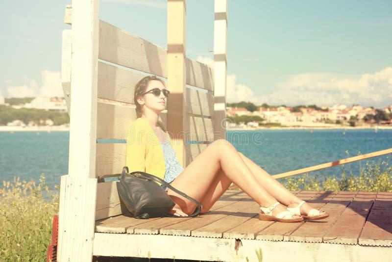 Jeune fille détendant par la mer Rétro photo modifiée la tonalité photos stock