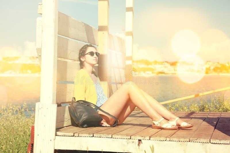 Jeune fille détendant par la mer Rétro photo modifiée la tonalité image stock