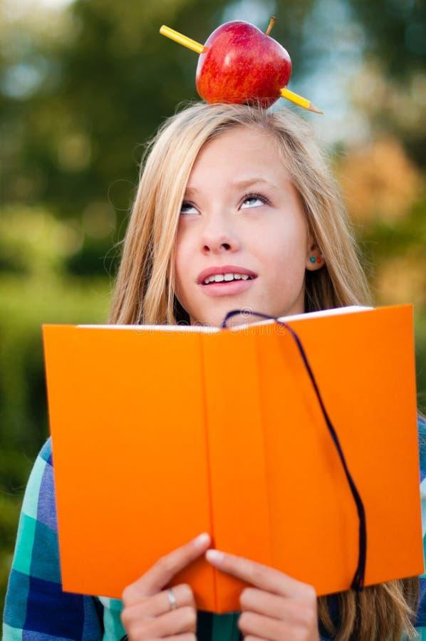 Jeune fille d'étudiant avec la pomme sur sa tête photos libres de droits