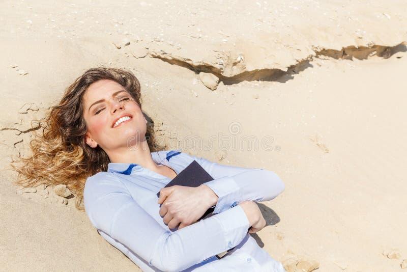 Jeune fille d'étudiant détendant sur la plage images stock