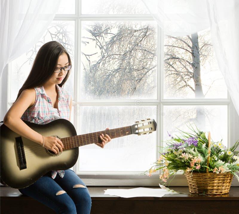 Jeune fille d'étudiant jouant la musique sur la guitare photos libres de droits