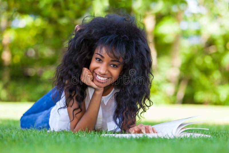 Jeune fille d'étudiant lisant un livre en parc d'école - p africain image stock