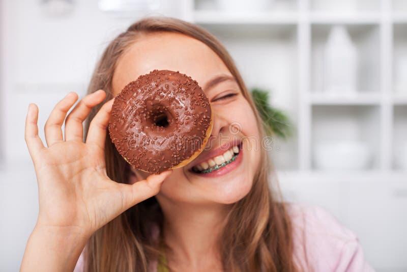 Jeune fille d'adolescent ayant l'amusement avec un beignet images stock